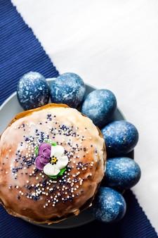 Gâteau de pâques décoré de fleur de sucre et d'oeufs de couleur bleue sur une plaque sur une surface en tissu blanc et bleu