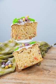 Gâteau de pâques découpé à base de pâte à levure, décoré de mousse comestible avec un nid et des œufs en chocolat. la surface poreuse du gâteau
