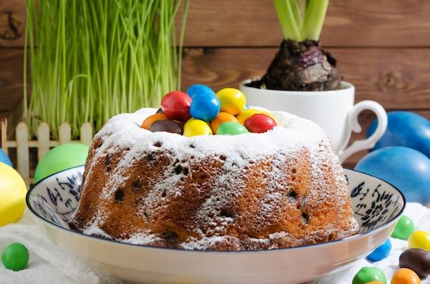 Gâteau de pâques avec du sucre en poudre et des pâtisseries sur fond rustique en bois