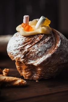 Gâteau de pâques élégant avec des guimauves et de la gelée porte sur un fond en bois rustique foncé.