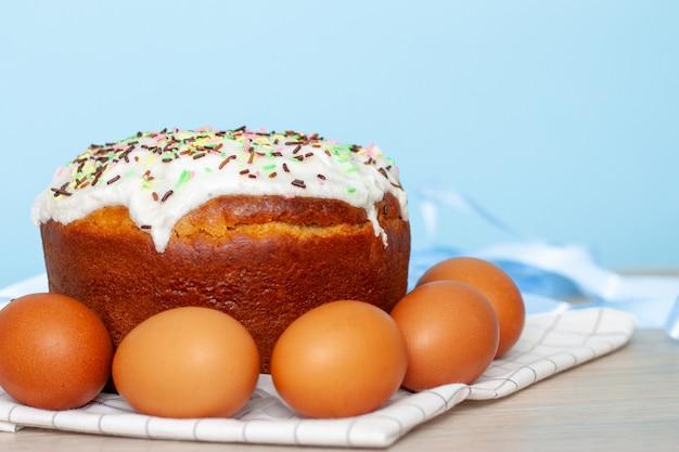 Gâteau de pâques et oeufs colorés sur fond bleu
