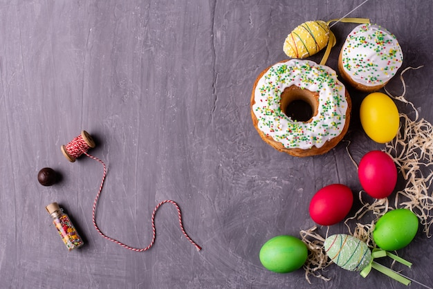 Gâteau de pâques et oeufs colorés sur fond sombre