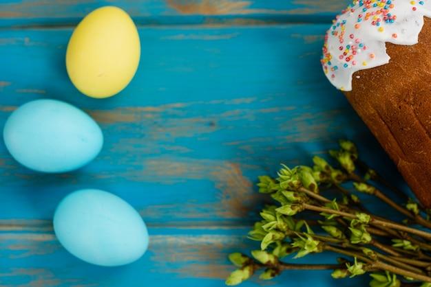 Gâteau de pâques et oeufs colorés sur une table en bois.