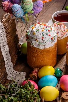 Gâteau de pâques et oeufs colorés avec tasse de thé