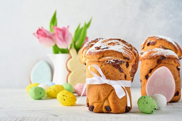 Gâteau de pâques, oeufs lumineux, pain d'épices et branches de saules sur une table festive de pâques. carte de voeux.