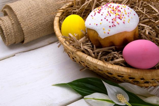 Gâteau de pâques et oeufs de pâques colorés dans un panier de nid, un sac et des fleurs sur une surface en bois blanche