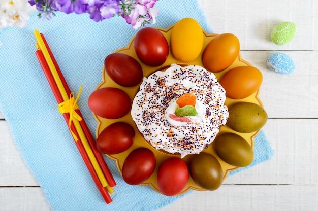 Gâteau de pâques et oeufs peints sur une assiette sur un fond en bois. thème de pâques. vue de dessus.