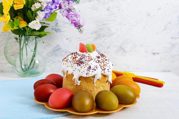 Gâteau de pâques et oeufs peints sur une assiette sur un fond en bois