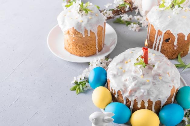 Gâteau de pâques et oeufs peints en jaune sur une table grise décorée de fleurs de printemps.