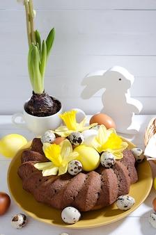 Gâteau de pâques avec des œufs teints dans un nid, des jonquilles et une jacinthe dans une tasse sur un fond en bois rustique blanc