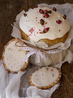 Gâteau de paques. pain sucré traditionnel de pâques décoré de meringue et de roses sèches roses, biscuits en forme de beaux œufs de pâques sur fond de bois. espace copie, mise au point sélective, gros plan