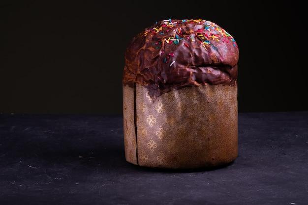 Un gâteau de pâques parsemé de chocolat et parsemé de bonbons se tient sur une surface noire