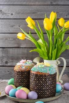 Gâteau de pâques, peint des oeufs avec des tulipes sur un fond en bois ancien rustique.