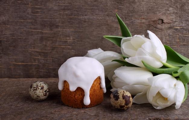 Gâteau de pâques, tulipes blanches, oeufs de caille sur un fond en bois rustique.