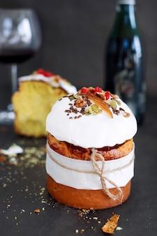 Gâteau de pâques et verre de vin rouge. composition de pâques avec du pain sucré orthodoxe, kulich et une bouteille de vin sur fond sombre