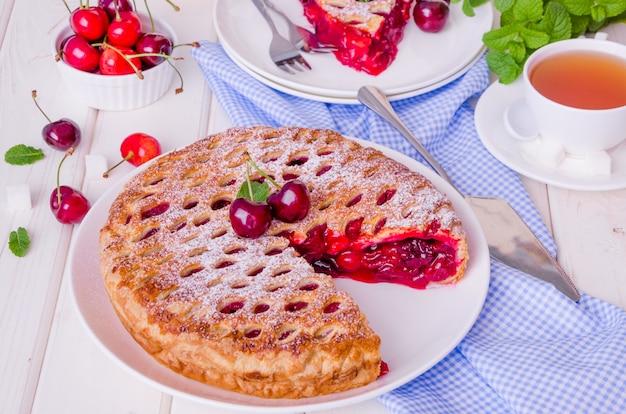 Gâteau de pâte feuilletée fermé avec des cerises de remplissage sur un fond en bois blanc.