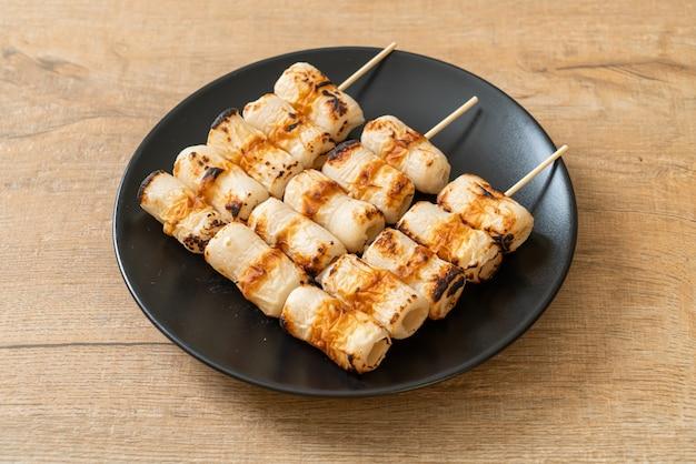 Gâteau de pâte de poisson grillé en forme de tube ou brochette de calmar en tube sur assiette