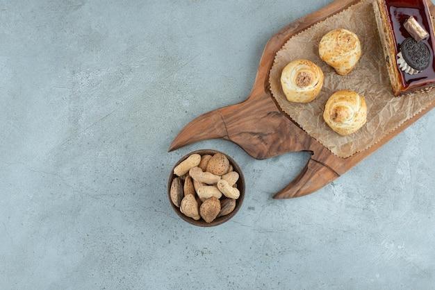 Gâteau et pâtisseries sur planche de bois avec des noix.