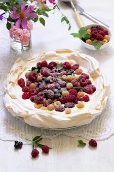 Gâteau pavlova à la crème et aux baies et un bouquet de fleurs sur fond clair. style rustique, mise au point sélective.