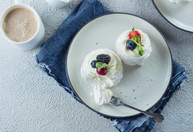 Gâteau pavlova fait maison avec des fruits frais et une tasse de café au lait.