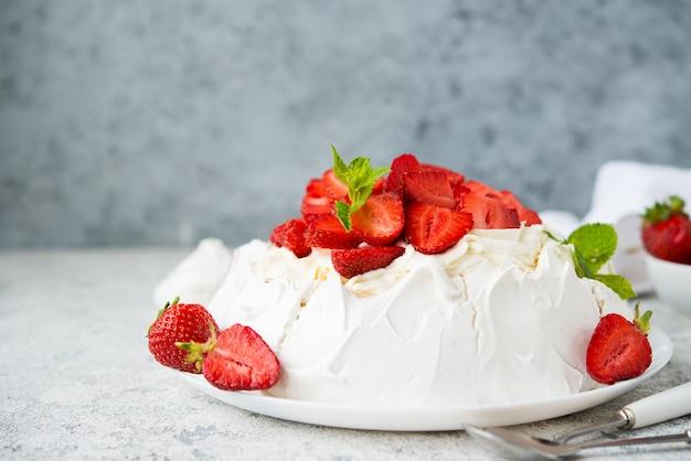 Gâteau pavlova avec meringue et fraises fraîches sur fond clair, mise au point sélective, espace de copie