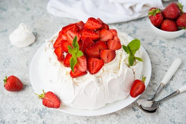 Gâteau pavlova avec meringue et fraises fraîches sur fond clair, mise au point sélective, gros plan