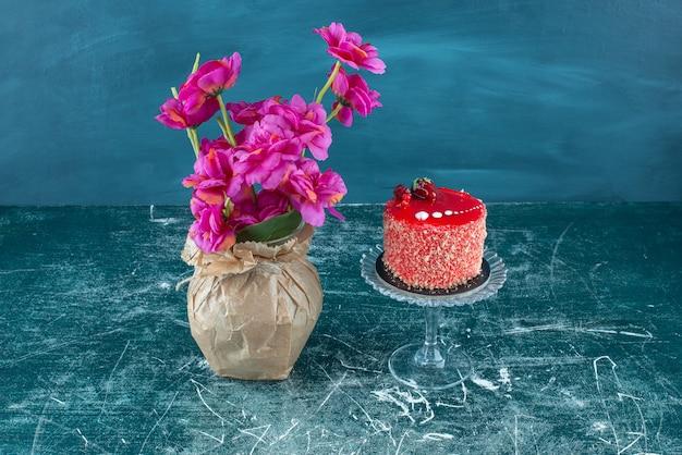 Gâteau sur un piédestal à côté d'un vase de fleurs sur fond bleu.