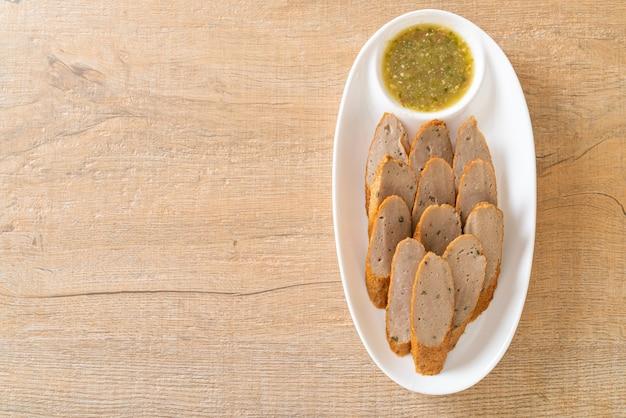 Gâteau de poisson chinois frit ou ligne de boulettes de poisson tranchées avec une trempette épicée aux fruits de mer