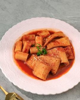 Gâteau de poisson coréen focus odeng sélectionné avec topokki (tteokbokki) sur plaque rose, espace de copie pour le texte