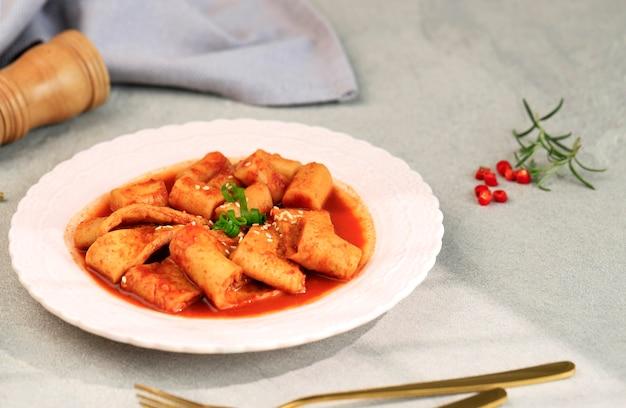 Gâteau de poisson coréen odeng avec topokki (tteokbokki) sur plaque rose, copiez l'espace pour le texte