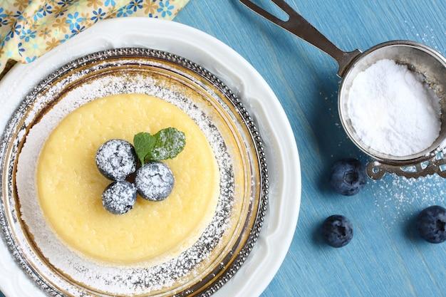 Gâteau pouding au citron surprise servi avec des baies sur une assiette
