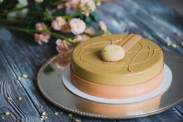 Gâteau de pudding jaune fraîchement cuit au four avec dacquoise aux amandes, confit de framboise, couche croustillante aux noisettes caramélisées et poudre de framboise