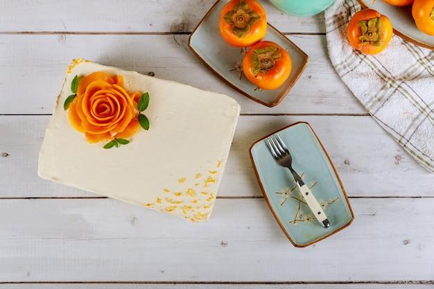 Gâteau rectangulaire crème au beurre blanc avec des fleurs roses de kaki