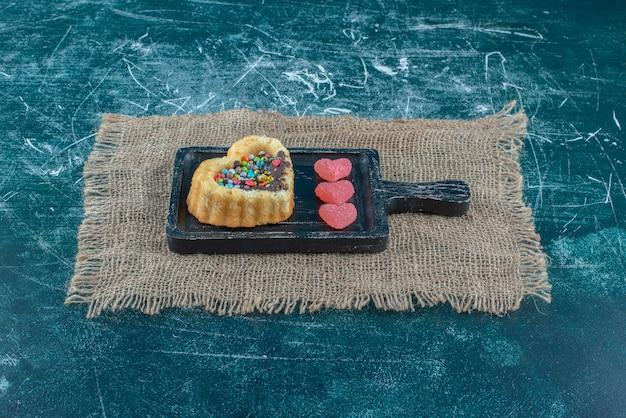 Gâteau rempli de chocolat et de bonbons et confitures en forme de coeur dans un petit plateau sur fond bleu. photo de haute qualité