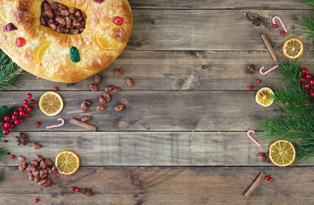 Gâteau roi sur une base en bois avec des décorations de noël. dessert typique des trois rois en espagne. vue de dessus.