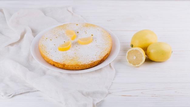 Gâteau rond au citron décoré servi dans une assiette avec des citrons sur du tissu