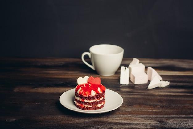 Gâteau rond rouge dans une soucoupe, une tasse de bonbons au thé ravissent les bonbons