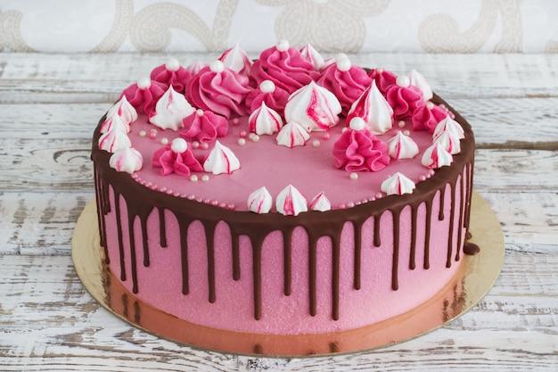 Gâteau rose aux meringues avec des taches de chocolat sur un fond en bois blanc