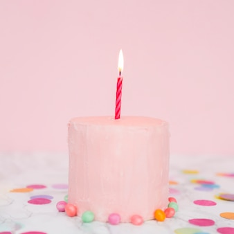 Gâteau rose avec une bougie allumée