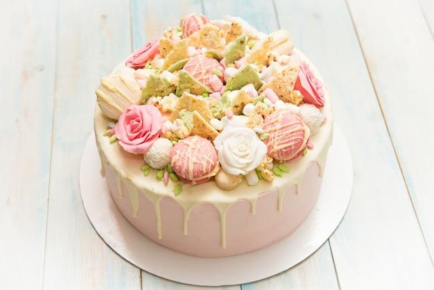 Gâteau rose avec des fleurs et des petits gâteaux sur une plaque blanche