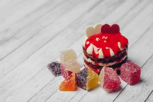 Gâteau rouge bonbons marmelade au chocolat fond en bois vue de dessus snack