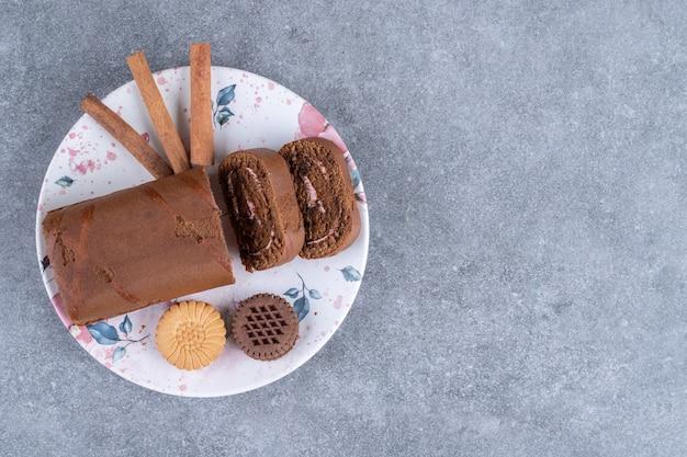 Gâteau roulé au chocolat, biscuits et bâtons de cannelle sur une assiette colorée