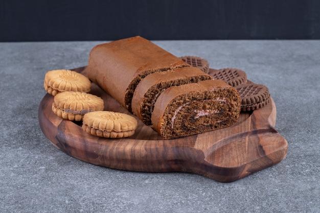 Gâteau roulé au chocolat et biscuits sur plaque de bois