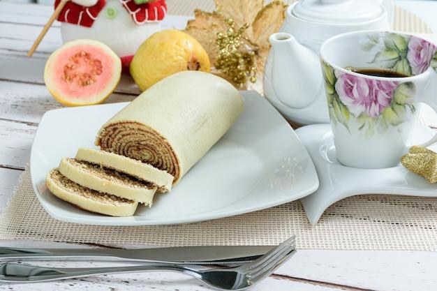 Gâteau roulé bolo de rolo tranché à côté d'une tasse de café et de goyaves.