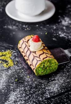 Gâteau roulé à la pistache émincée et crème à la vanille et aux cerises.