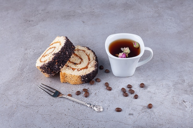 Gâteau roulé en tranches sur planche de bois avec tasse de thé sur la surface de la pierre.