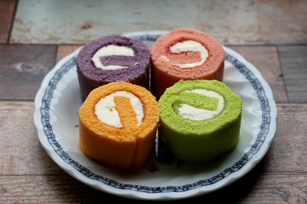 Gâteau de rouleau de confiture multicolore sur la plaque sur une table en bois