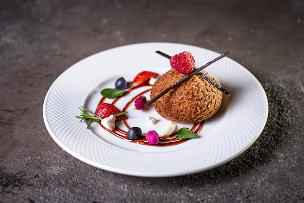 Gâteau sablé au dessert avec du chocolat et des baies sur une plaque blanche