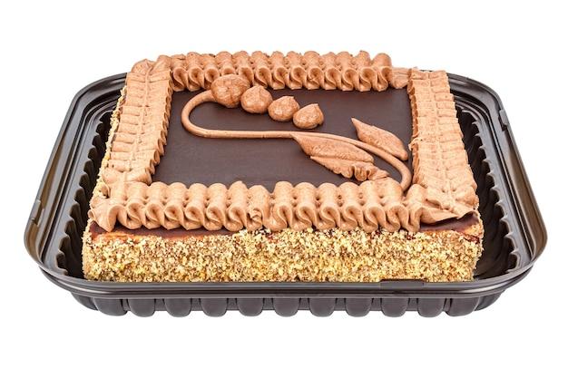 Gâteau sablé avec glaçage au chocolat et décoré par ornement crème et figure de fleur dans un emballage en plastique ouvert isolé sur blanc