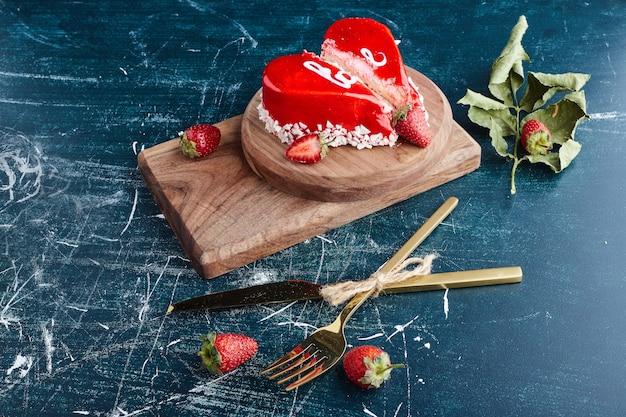 Gâteau de la saint-valentin en forme de coeur avec de la crème rouge.